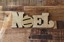 Word Noel in gold on a wooden floor type background