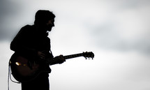 Silhouette of man playing guitar at dusk.