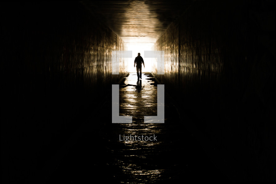 Man walking towards a light shaped cross formed by reflections on the walls, ceiling and floor of an underground concrete culvert.