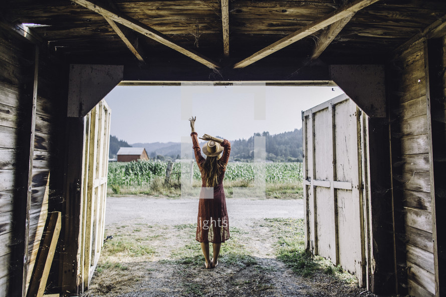 a woman in a dress and cowgirl hat standing at the entrance of a barn