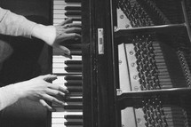 hands playing piano keys