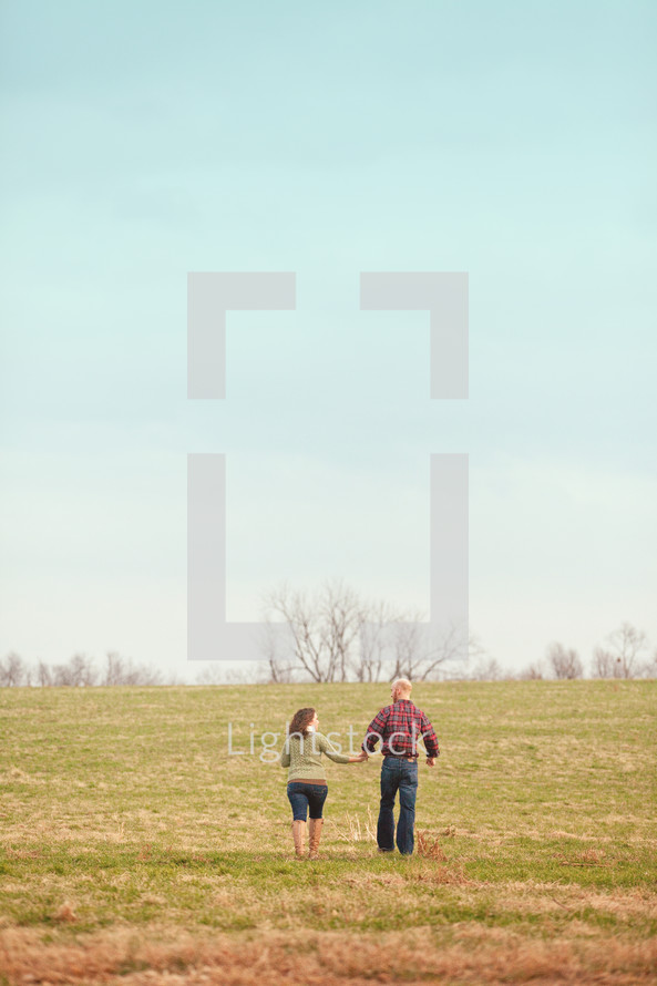 couple walking in a field holding hands