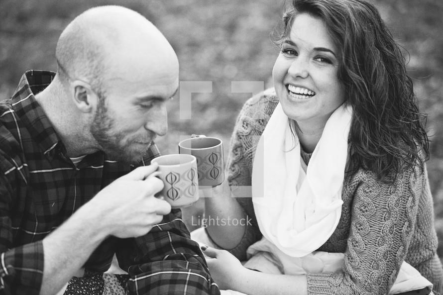 Couple enjoying coffee outside.