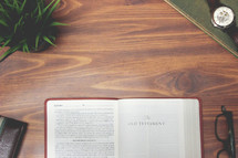 open Bible and reading glasses on a wood table - The Old Testament