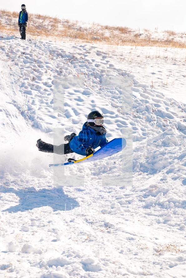 child sledding on a snow day