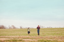 Couple running through a field.