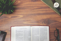 open Bible and reading glasses on a wood table - Galatians