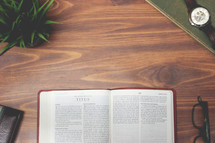 open Bible and reading glasses on a wood table - Titus