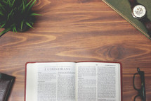 open Bible and reading glasses on a wood table - 2 Corinthians