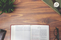 open Bible and reading glasses on a wood table - Acts