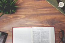 open Bible and reading glasses on a wood table - Genesis