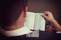 a man looking down reading a Bible