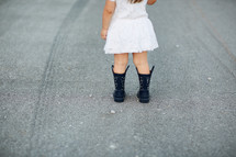 a toddler in rain boots and a dress