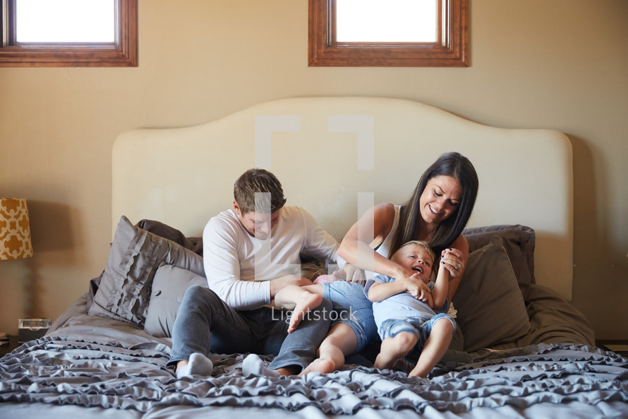 a family sitting on a bed