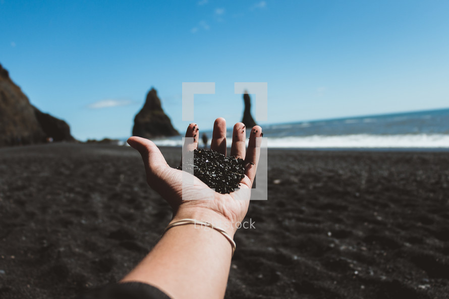 a person holding black sand standing on a beach