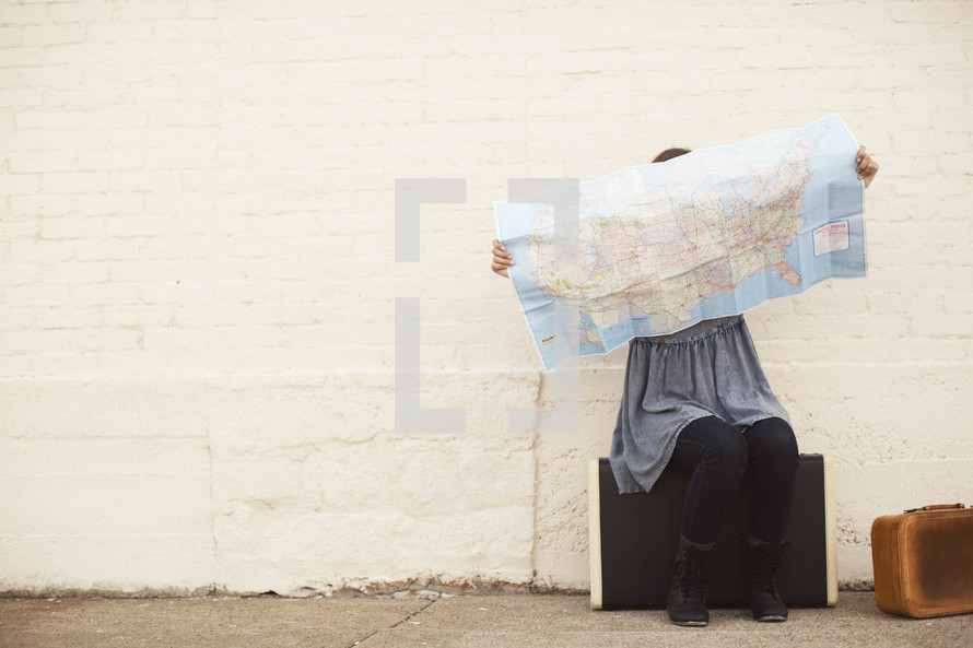 woman sitting on suitcases looking at a map