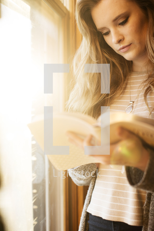 a teenage girl reading a Bible standing by a window