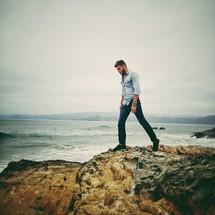 man walking on a rocky shore