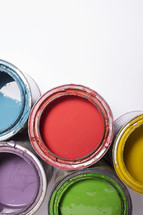 Open cans of brightly colored paints.