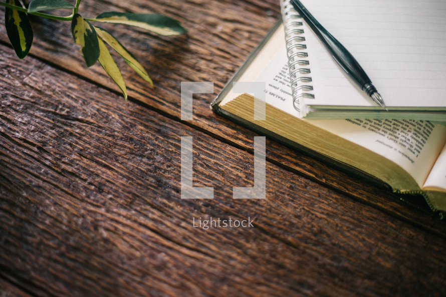 pencil, notebook, and open Bible on a wood background