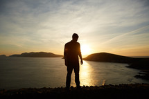 silhouette of a man standing by a shore at sunset