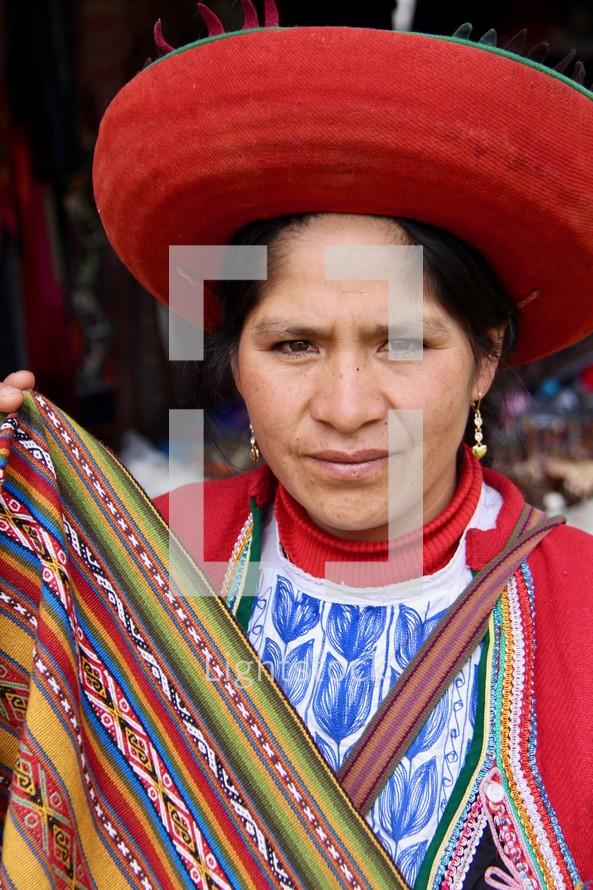 Peruvian woman holding woven blanket