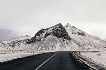 snow on a mountain and curve in a road