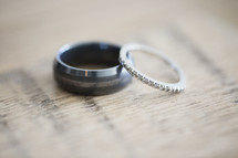 Close up of two wedding bands on a wood table.