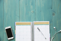 planner, cellphone, earbuds, and pen on a turquoise blue desk