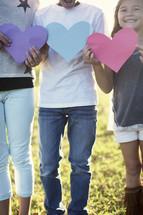 children holding paper hearts