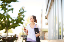 a woman carrying a yoga mat and listening to her phone