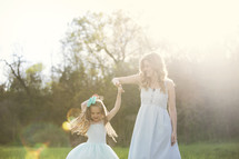 mother and daughter dancing under sunlight