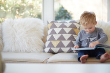 a toddler boy sitting on a couch reading a book