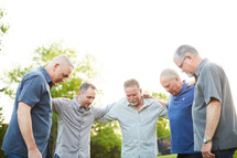 men standing in a backyard praying together