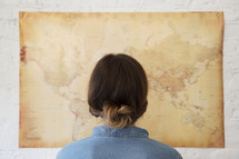 a woman looking at a world map on a wall.