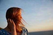 a woman tucking her hair behind her ear