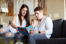 a mother and father reading a children's book to their kids on the couch