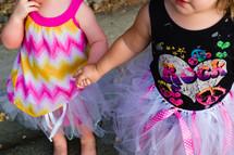toddler girls in tutus holding hands