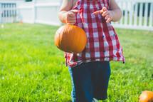 a toddler carrying a small pumpkin