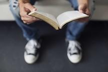 a teen boy reading a Bible