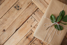 holly on a brown paper gift on a  wood background
