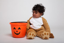 toddler boy in a Halloween costume with a jack-0-latern candy bucket