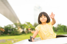 a little girl waving out of a sunroof