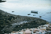 a boat anchored in shallow water along a shore