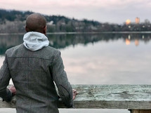 man looking out at a city scene across a lake
