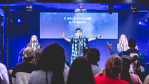 people on stage singing at a worship service