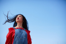 portrait of a young woman standing outdoors looking up