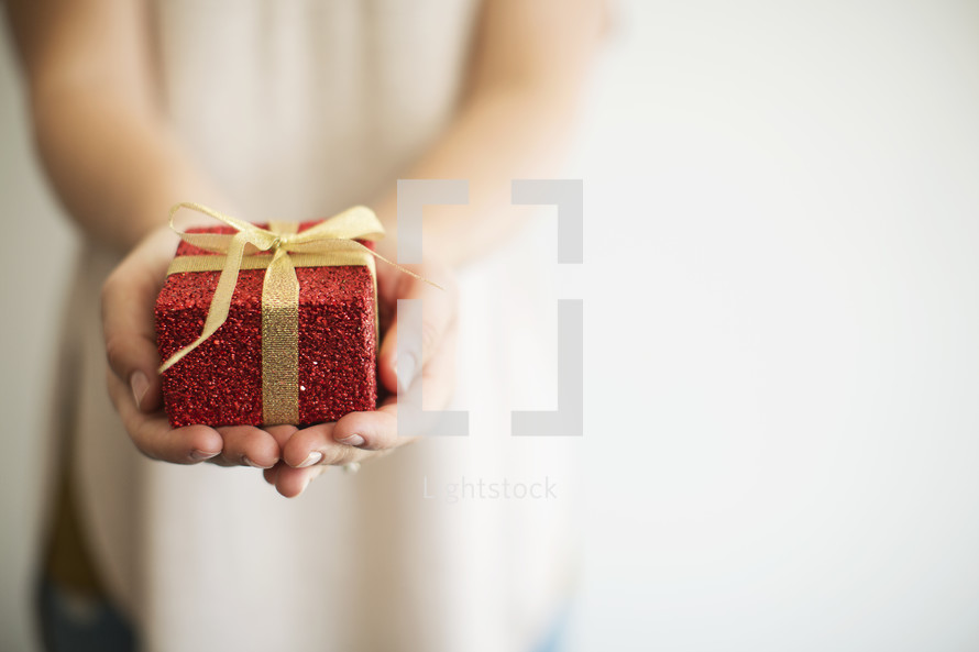 a woman holding out a wrapped Christmas gift