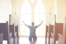 a man kneeling with his hands raised in worship at church