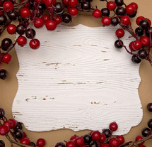 red berries around white wood sign